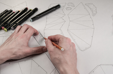 Male designer makes a working drawing. Workplace of a toy designer. Markers, ruler, pen and pencil are on the drawing Stock Photo