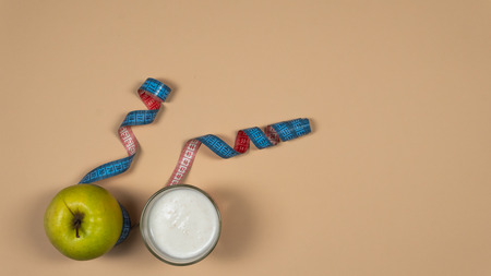 Concept diet - healthy food with apple, yogurt and measuring tape on yellow background. White dishes and glass cup