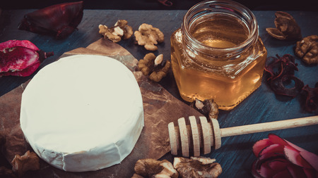 Healthy and tasty food. Camembert cheese with nuts and honey. Dried flowers on the dark background