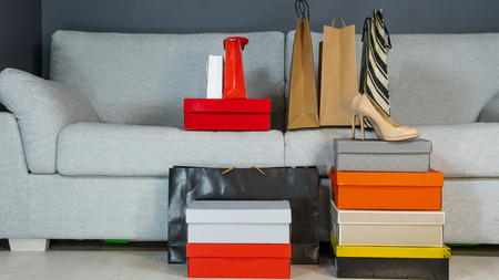 boxes with shoes and shopping bags on the background of a gray sofa