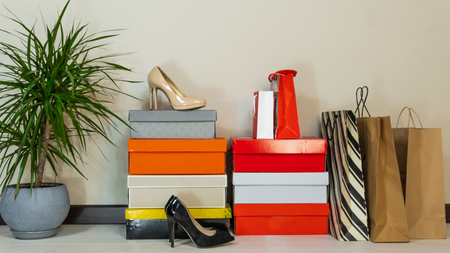 boxes with shoes and shopping bags on the background of a light wall