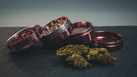 Marijuana buds and joint lie on a dark gray background. Grinder  near cannabis. Marijuana is medicine.