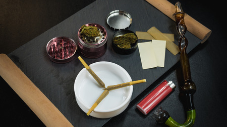Marijuana joints lie in the ashtray. Smoking pipe, grinder, cannabis. Cannabis is herbal medicine Banco de Imagens