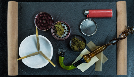 Marijuana joints lie in the ashtray. Smoking pipe, grinder, cannabis. Cannabis is herbal medicine 免版税图像