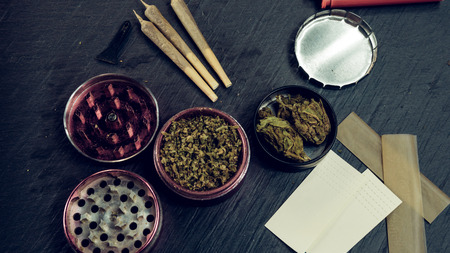 Marijuana buds, joints, paper and lighter lie on dark grey background. Cannabis is herbal medicine