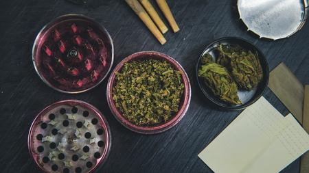 Marijuana buds, joints, paper and lighter lie on dark grey background. Cannabis is herbal medicine Banco de Imagens - 122084384