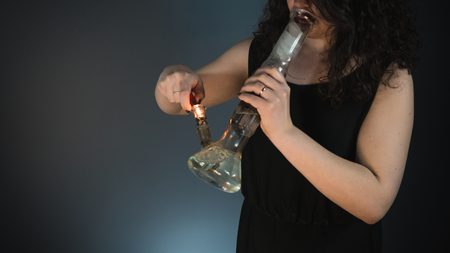 The young person smoking medical marijuana with bong. Close-up. Cannabis is medicine