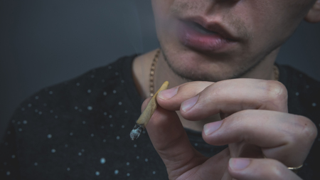 The young person smoking medical marijuana joint. Close-up. Cannabis is medicine