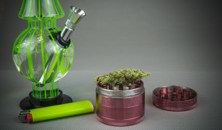 Medical marijuana buds with bong and grinder close-up. Cannabis is medicine
