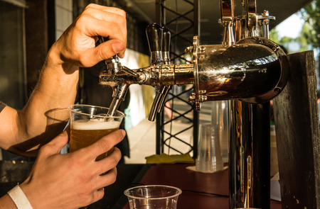 The male bartender pouring beer into a glass close-up. Street food. A glass with cold beer in the bartenders hands