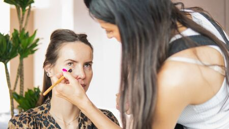 Makeup artist doing professional makeup for young woman. Woman applying by professional make up master. Beautiful model girl indoors. Stok Fotoğraf