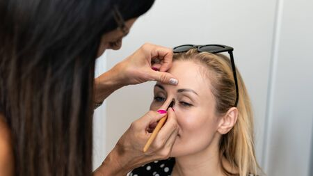 Makeup artist doing professional makeup for young woman. Woman applying by professional make up master.