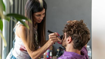 Makeup artist doing professional makeup for young man. Man applying by professional make up master. Beautiful model man indoors.
