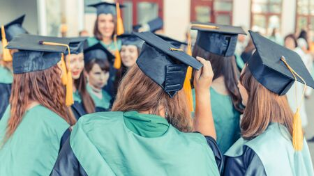 A group of young female graduates. Female graduate is smiling against the background of university graduates. Concept of education, graduation and knowledge.
