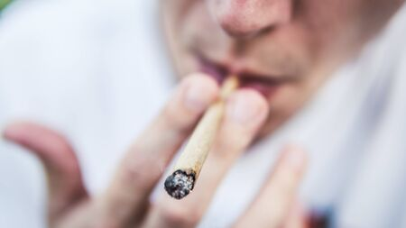 The young person smoking medical marijuana joint outdoors. The young man smoke cannabis blunt, close-up. Cannabis is a concept of herbal medicine. Imagens