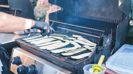 Sliced zucchini, grilled, picnic with barbecue in the open air. squash barbecue roasted on metal grill. Diet vegan bbq. Cooking vegetables on the grill outdoors Stockfoto
