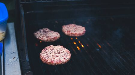 Burger cutlet grilled, picnic with barbecue in the open air. Cutlet barbecue roasted on metal grill. The person cooking burger. Cooking meat on the grill outdoors