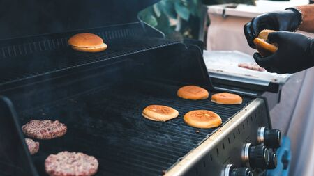 Burger cutlet and bun grilled, picnic with barbecue in the open air. Cutlet barbecue roasted on metal grill. The person cooking burger. Cooking meat and roll on the grill outdoors