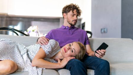Millennial couple in love relaxing together on sofa at home. Happy couple looking to each other and laugh. Focus on girl Stock Photo