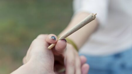 Close-up of females hands holding marijuana joint, smoking cannabis blunt outdoors. Cannabis is a concept of herbal medicine