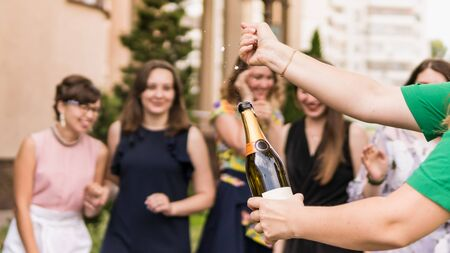 Young woman opening a bottle of champagne with female friends standing in background laughing and having fun. Young people celebrating with champagne at party outdoors. Concept of hen-party or corporate 版權商用圖片