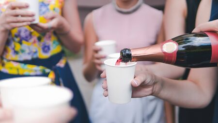 Young woman pouring champagne into glass, close-up outdoors. Young people celebrating with champagne at party outdoors. Concept of hen-party or corporate Stockfoto