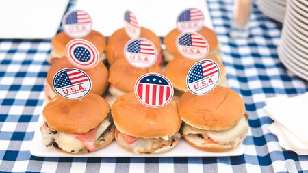 Close-up of fresh burger with American flag on the table. Tasty burger with cheese, meat, onion and tomatoes served outdoor. Concept of catering service and outdoors party
