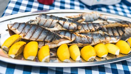 Close-up of grilled fish with lemon on the table. Tasty fish with lemon served outdoor. Concept of catering service and outdoors party