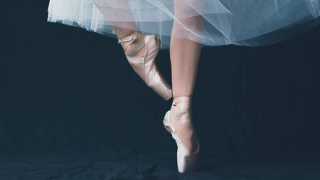 Close-up of dancing legs of ballerina wearing white pointe on a black background. Ballet dancer and practice concept background
