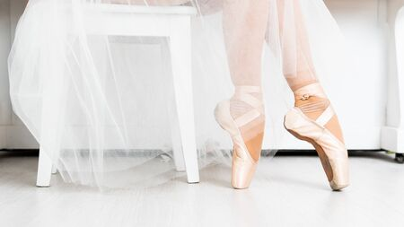 Close-up of dancing legs of ballerina wearing white pointe on a white background. Ballet dancer and practice concept background
