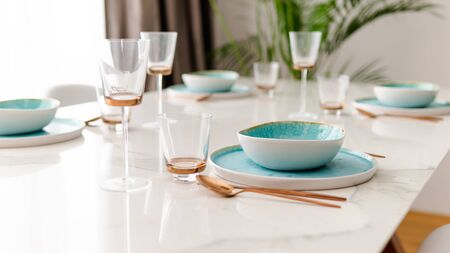 Close-up of served table in a luxury restaurant at the holiday eve. Serving dishes, glass wine glasses and gold cutlery. Concept of catering service.