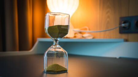 Sand running through the bulbs of an hourglass. Hourglass as time passing concept for business deadline Banco de Imagens