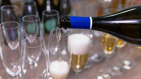 Close-up of champagne pouring into a wine glass. Concept of restaurant, bar and catering service