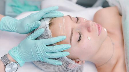 The female dermatologist do face massaged to beautiful girl cosmetology cabinet or beauty clinic. Concept of face cleanser, skin and health care