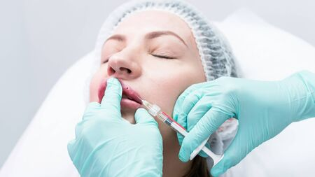 The young beautician doctor preparing to making injection in female lips. The doctor cosmetologist makes lip augmentation procedure. Concept of beauty salon and plastic surgery clinic.