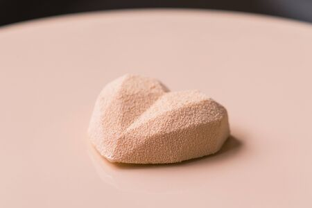 Close-up of confectioner decorates the cake with velour using the spray gun. Modern French mousse pastry dessert with chocolate velour. Heart shape