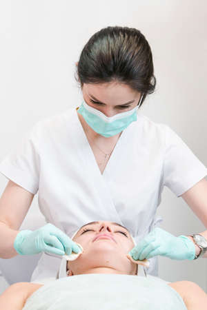 The young female client of cosmetic salon having a face cleaning procedure. The doctor cosmetologist cleaning skin with sponge. Concepts of skin care and beauty salon or clinic.