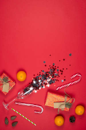 Glass of champagne with confetti, New Year and Christmas presents, handmade gift boxes wrapped with red paper and decorated fir tree branches, flat lay. Copy space. Concepts of greeting card. Top view.
