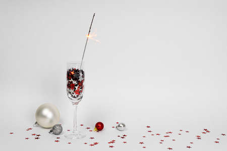 Glasses of champagne with confetti in shape of stars and sparkler on white background, Christmas decorations around, copy space. Concepts of greeting and New Year eve. Foto de archivo