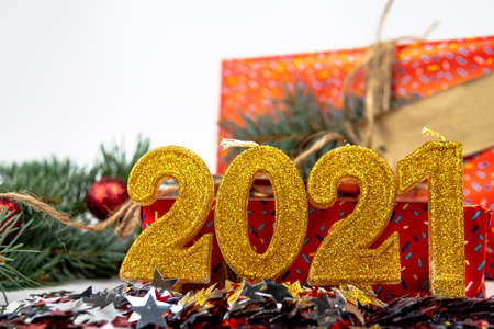Holiday background with the text of the golden number 2021, confetti, gift box and Christmas tree branch are on the background. Happy New Year and holiday concept. Selective focus. 免版税图像