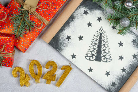 Silhouette of Christmas tree made of flour. Holiday background with the text of the golden number 2021, gift box and tree branch, top view. Concept of Christmas dinner preparation