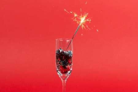 Glasses of champagne with confetti in shape of stars and sparkler on red background, Christmas decorations, copy space. Concepts of greeting card and New Year eve.