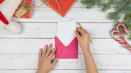 The young girl written letter to Santa Claus and puts them in an envelope, flat lay. Christmas decorations and gift box on wooden desk, top view. Concept of New Year eve. Foto de archivo