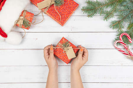 Female hands opening a gift box wrapping in the red paper, flat lay. Preparing for Christmas holidays. Top view of hands on wooden table with fir tree branches and Santa Claus hat.