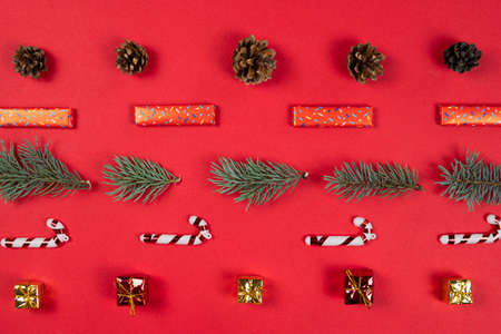 Christmas abstract pattern, flat lay. Fir tree branches, gift box and cone on red background. Concept of New Year presents, festive and holiday shopping. Top view.