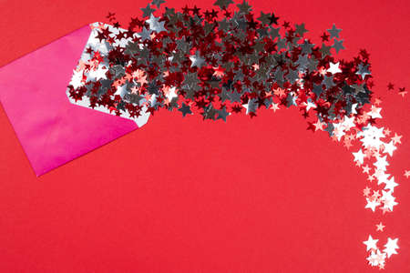 Christmas background, flat lay. The open pink envelope with confetti in form of star on red background. Top view. Concept of New Year presents, festive and holiday shopping