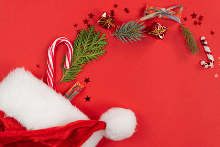 Christmas background, flat lay. Santa Claus hat with decoration and fir tree branches on red background. Top view. Concept of New Year presents, festive and holiday shopping Foto de archivo