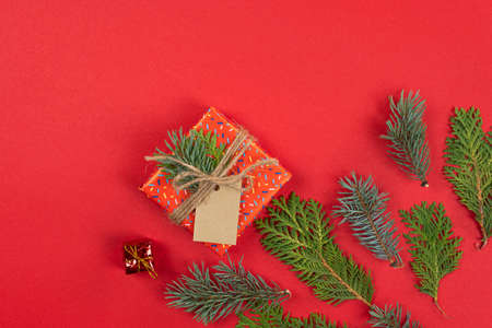 Christmas background, flat lay. Fir tree branches and gift box on red background. Top view. Concept of New Year presents, festive and holiday shopping