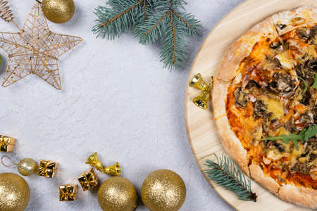 Flat lay of pizza spinning 360 degree rotation on wooden salver, Christmas decorations around. Concept of discount and promotion in a pizzeria. Copy space, top view. 免版税图像