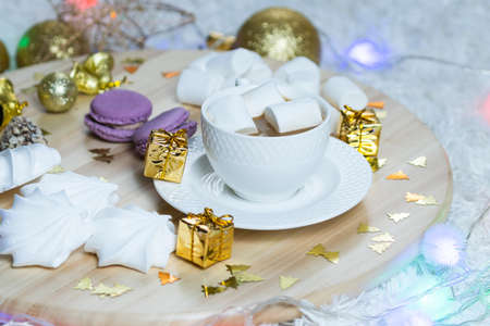 A cup of coffee with milk and marshmallows and garland on wooden salver, other sweets and Christmas decorations around. Concept of New Year presents, festive and holiday
